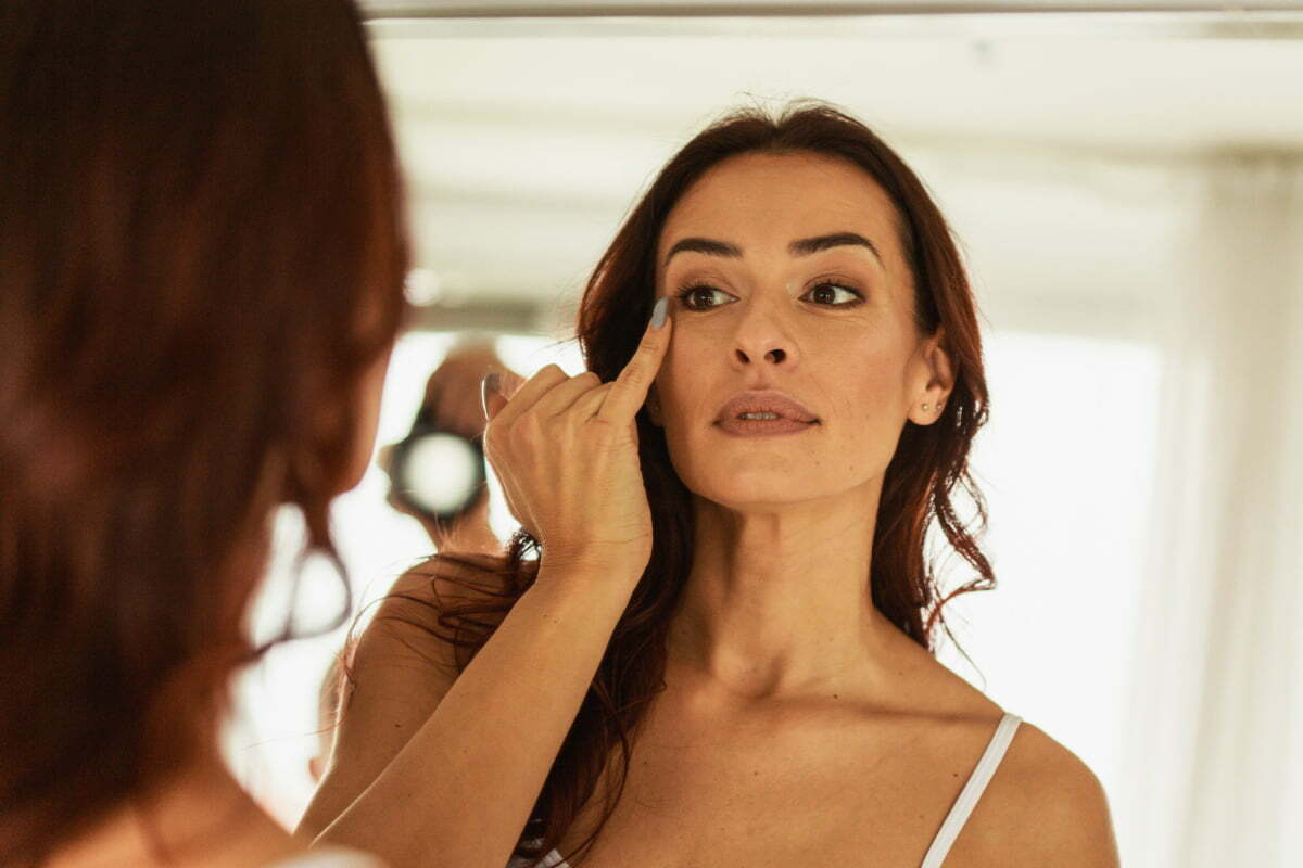 Mature Woman Examines Crows Feet Wrinkles in Mirrors for Signs of Aging